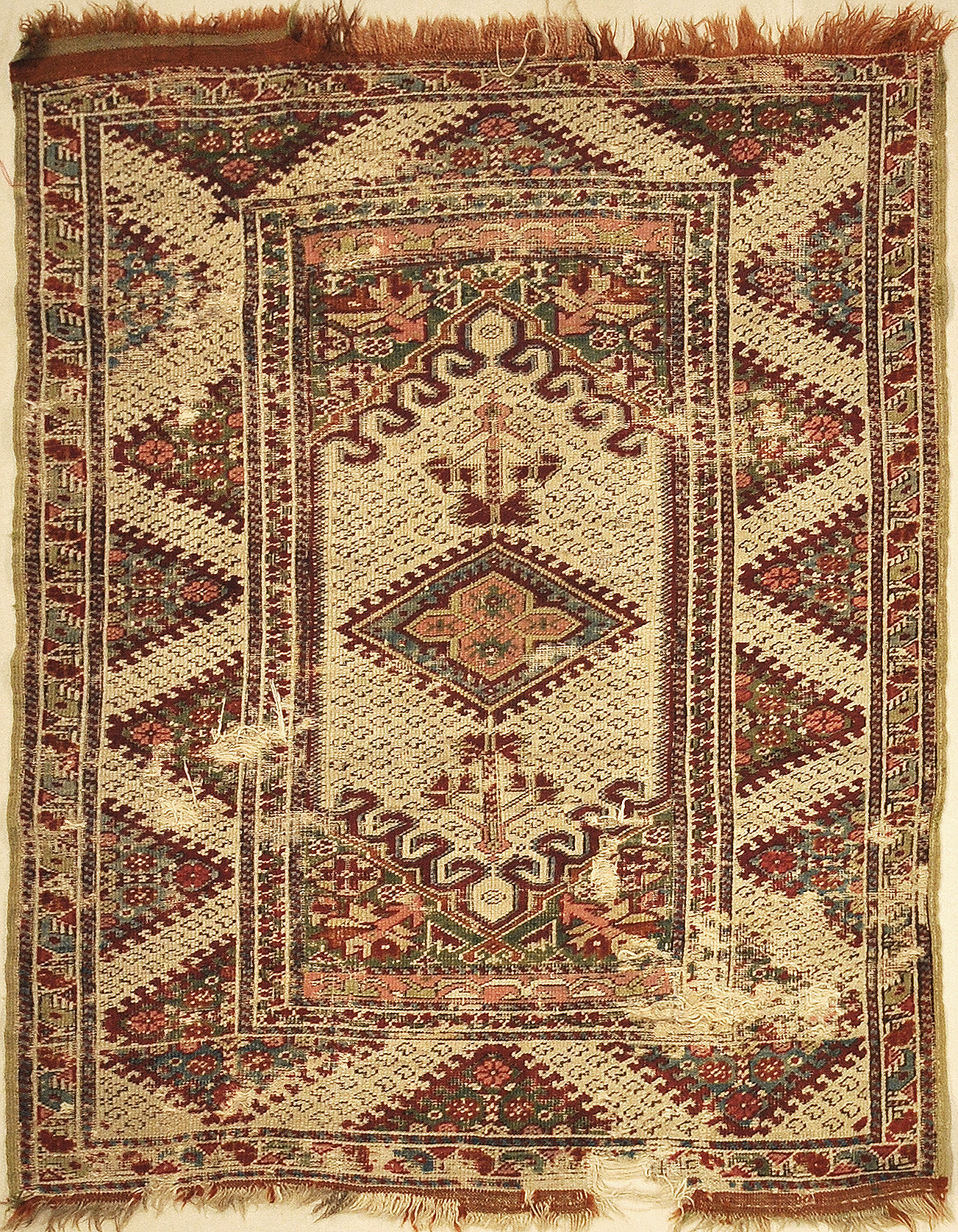 Antique Ghiordes Rug Circa 17th Century. A piece of genuine authentic antique woven carpet art sold by the Santa Barbara Design Center, Rugs and More.